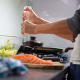 Νέα γυναίκα που καρυκεύει ένα δίχτυ salomn στη σύγχρονη κουζίνα της Στοκ Εικόνες