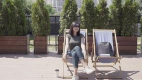 Νέα γυναίκα που καταγράφει τα βιβλία και που απολαμβάνει μια ηλιόλουστη ημέρα, που παίρνει μια βαθιά εισπνοή φιλμ μικρού μήκους