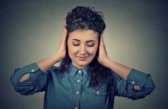 Νέα γυναίκα που καλύπτει και τα δύο αυτιά με τα χέρια της Στοκ Φωτογραφία