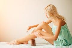 Νέα γυναίκα που κηρώνει το χαμηλότερο πόδι της με το μέλι Στοκ φωτογραφία με δικαίωμα ελεύθερης χρήσης