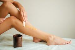 Νέα γυναίκα που κηρώνει το χαμηλότερο πόδι της με το μέλι Στοκ Φωτογραφία