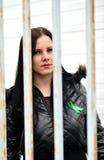 Νέα γυναίκα που κοιτάζει από πίσω από τους φραγμούς Στοκ Εικόνες