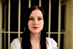 Νέα γυναίκα που κοιτάζει από πίσω από τους φραγμούς Στοκ φωτογραφία με δικαίωμα ελεύθερης χρήσης