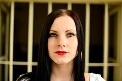 Νέα γυναίκα που κοιτάζει από πίσω από τους φραγμούς Στοκ Φωτογραφία