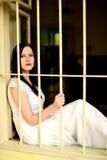 Νέα γυναίκα που κοιτάζει από πίσω από τους φραγμούς Στοκ Φωτογραφίες