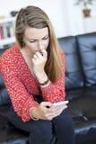 Νέα γυναίκα που κοιτάζει επίμονα στα κινητά καρφιά της τηλεφώνων και δαγκώματος καθμένος σε έναν καναπέ δέρματος στοκ φωτογραφία με δικαίωμα ελεύθερης χρήσης