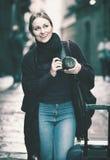 Νέα γυναίκα που κοιτάζει και που παίρνει τις εικόνες υπαίθρια Στοκ Φωτογραφία