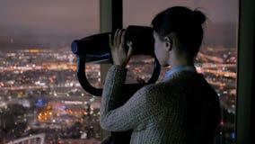 Νέα γυναίκα που κοιτάζει μέσω του τηλεσκοπίου τουριστών και που ερευνά τη εικονική παράσταση πόλης νύχτας φιλμ μικρού μήκους