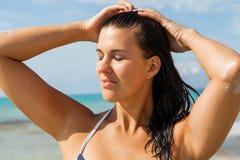 Νέα γυναίκα που κοιτάζει μακριά στην παραλία στοκ φωτογραφία