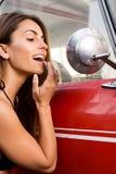 Νέα γυναίκα που κοιτάζει στον εξωτερικό καθρέφτη από το εκλεκτής ποιότητας αυτοκίνητο Τρόπος ζωής Καλιφόρνιας στοκ εικόνες με δικαίωμα ελεύθερης χρήσης