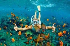 Νέα γυναίκα που κολυμπά με αναπνευτήρα με τα ψάρια κοραλλιογενών υφάλων στοκ εικόνα