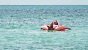 Νέα γυναίκα που κολυμπά με το διογκώσιμο δαχτυλίδι απόθεμα βίντεο