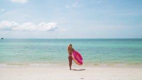 Νέα γυναίκα που κολυμπά με το διογκώσιμο δαχτυλίδι φιλμ μικρού μήκους