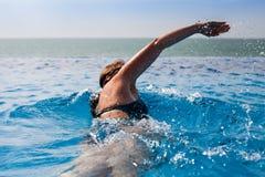 Νέα γυναίκα που κολυμπά σε μια λίμνη με την ωκεάνια άποψη Στοκ φωτογραφίες με δικαίωμα ελεύθερης χρήσης