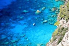 Νέα γυναίκα που κολυμπά στη διαφανή ιόνια θάλασσα κοντά στη βάρκα Άποψη από Angelokastro στο νησί της Κέρκυρας, Ελλάδα Στοκ φωτογραφία με δικαίωμα ελεύθερης χρήσης