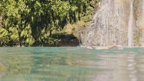 Νέα γυναίκα που κολυμπά στο μπλε νερό της λίμνης από το ράντισμα του καταρράκτη Ευτυχής γυναίκα που κολυμπά στη λίμνη και το νερό φιλμ μικρού μήκους