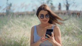 Νέα γυναίκα που κουβεντιάζει με τους φίλους από το smartphone στο ηλιόλουστο πάρκο απόθεμα βίντεο