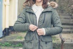 Νέα γυναίκα που κουμπώνει το παλτό της έξω στοκ εικόνες