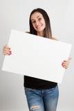 Νέα γυναίκα που κρατά έναν λευκό πίνακα Στοκ Εικόνα