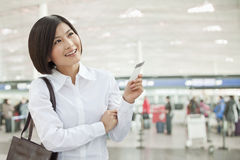 Νέα γυναίκα που κρατά ένα εισιτήριο αεροπλάνων Στοκ Εικόνα