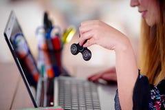 Νέα γυναίκα που κρατά ένα δημοφιλές fidget παιχνίδι κλωστών στο χέρι της ενώ εργάζεται στον υπολογιστή της στο υπόβαθρο γραφείων Στοκ φωτογραφία με δικαίωμα ελεύθερης χρήσης