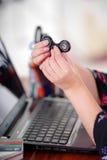 Νέα γυναίκα που κρατά ένα δημοφιλές fidget παιχνίδι κλωστών στο χέρι της ενώ εργάζεται στον υπολογιστή της στο υπόβαθρο γραφείων Στοκ εικόνες με δικαίωμα ελεύθερης χρήσης
