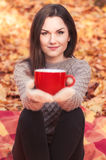 Νέα γυναίκα που κρατά ένα μεγάλο κόκκινο φλυτζάνι Στοκ Εικόνα