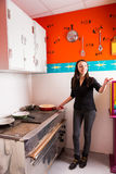 Νέα γυναίκα που κρατά ένα τηγάνι και που δείχνει σε κάποιο στεμένος στοκ εικόνα με δικαίωμα ελεύθερης χρήσης