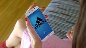 Νέα γυναίκα που κρατά ένα τηλέφωνο κυττάρων με τη φόρτωση Adidas κινητό app Η εννοιολογική εκδοτική CGI Στοκ εικόνες με δικαίωμα ελεύθερης χρήσης