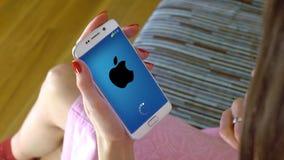 Νέα γυναίκα που κρατά ένα τηλέφωνο κυττάρων με τη φόρτωση Apple κινητό app Εννοιολογικός εκδοτικός 4K συνδετήρας απόθεμα βίντεο