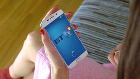 Νέα γυναίκα που κρατά ένα τηλέφωνο κυττάρων με τη φόρτωση British Telecom κινητό app Η εννοιολογική εκδοτική CGI Στοκ Φωτογραφία