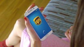 Νέα γυναίκα που κρατά ένα τηλέφωνο κυττάρων με τη φόρτωση UPS κινητό app Η εννοιολογική εκδοτική CGI Στοκ εικόνα με δικαίωμα ελεύθερης χρήσης