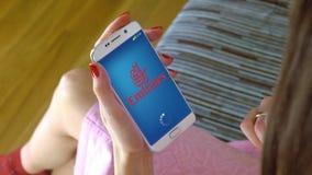 Νέα γυναίκα που κρατά ένα τηλέφωνο κυττάρων με τις αερογραμμές κινητό app εμιράτων φόρτωσης Η εννοιολογική εκδοτική CGI Στοκ Φωτογραφίες