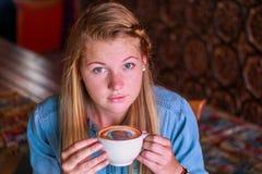 Νέα γυναίκα που κρατά ένα φλυτζάνι καφέ με το πρόσωπό της που τυπώνεται στον αφρό Στοκ Φωτογραφίες