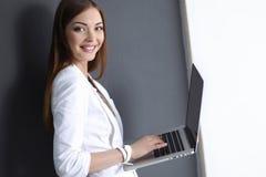 Νέα γυναίκα που κρατά ένα lap-top, που απομονώνεται στο γκρι Στοκ Εικόνες