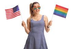 Νέα γυναίκα που κρατά μια αμερικανική σημαία σε ένα χέρι και ένα ουράνιο τόξο φ Στοκ εικόνες με δικαίωμα ελεύθερης χρήσης