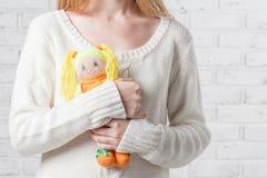 Νέα γυναίκα που κρατά μια κούκλα Αναχώρηση της παιδικής ηλικίας Στοκ φωτογραφία με δικαίωμα ελεύθερης χρήσης