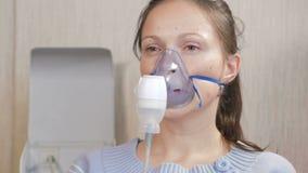 Νέα γυναίκα που κρατά μια μάσκα από inhaler στο σπίτι Μεταχειρίζεται την ανάφλεξη των εναέριων διαδρόμων μέσω nebulizer Παρεμπόδι φιλμ μικρού μήκους