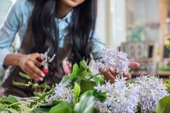 Νέα γυναίκα που κρατά τα όμορφα λουλούδια και τους τέμνοντες μίσχους Στοκ Φωτογραφίες