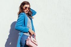 Νέα γυναίκα που κρατά τη μοντέρνη τσάντα και που φορά το καθιερώνον τη μόδα μπλε παλτό Θηλυκά ενδύματα και εξαρτήματα άνοιξη o στοκ φωτογραφία με δικαίωμα ελεύθερης χρήσης