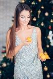 Νέα γυναίκα που κρατά το γλυκό μανταρίνι, την πορτοκαλιά διάθεση, τη διατροφή και τη νέα έννοια έτους στοκ φωτογραφία