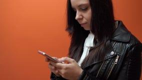 Νέα γυναίκα που κρατά το κινητό τηλέφωνο διαθέσιμο στο πορτοκαλί υπόβαθρο απόθεμα βίντεο