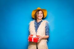 Νέα γυναίκα που κρατά το κόκκινο δώρο στα χέρια Στοκ φωτογραφία με δικαίωμα ελεύθερης χρήσης