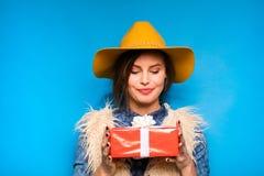 Νέα γυναίκα που κρατά το κόκκινο δώρο στα χέρια Στοκ Φωτογραφίες