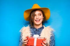 Νέα γυναίκα που κρατά το κόκκινο δώρο στα χέρια Στοκ Εικόνες