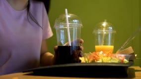 Νέα γυναίκα που κρατά το μη αλκοολούχο ποτό με το άχυρο, σπουδαστής που έχει το μεσημεριανό γεύμα στον καφέ, τρόφιμα στοκ φωτογραφίες