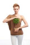 Νέα γυναίκα που κρατά το σε δοχείο φυτό Στοκ φωτογραφία με δικαίωμα ελεύθερης χρήσης