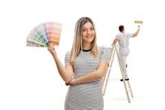 Νέα γυναίκα που κρατά swatch χρώματος με μια ζωγραφική ζωγράφων Στοκ εικόνα με δικαίωμα ελεύθερης χρήσης