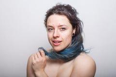 Νέα γυναίκα που κυλά τη ζωηρόχρωμη αλλά χαλασμένη ακατάστατη τρίχα της στο δάχτυλό της στοκ φωτογραφίες