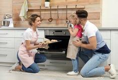 Νέα γυναίκα που μεταχειρίζεται την οικογένειά της με τα σπιτικά ψημένα φούρνος μπισκότα στοκ εικόνες